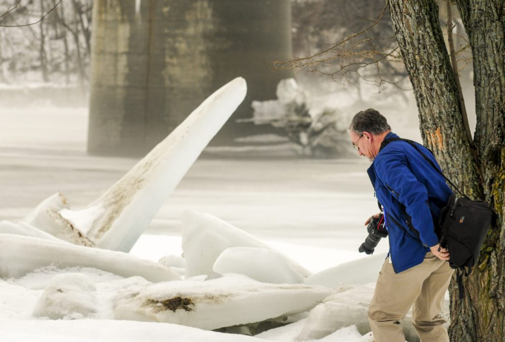 Tim True, of Chelsea, moves to get a better angle for photographing ice slabs Wednesday at the East Side Boat Launch in Augusta. Large chunks of ice lined both sides of the Kennebec River from last month's ice jam flooding.