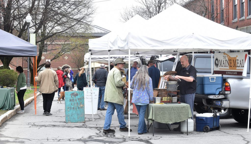 People browse among produce April 27, 2017, at the first farmers market of the season on Common Street in Waterville.