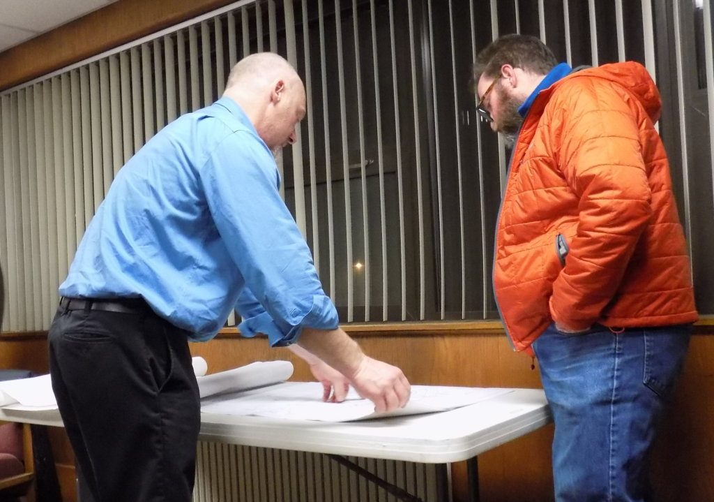 The Farmington Water Department is proposing to replace an outdated earthen reservoir off Anson Street with a smaller, more secure reservoir. Jim Lord, of Dirigo Engineering, left, shows project details to resident Steve Muise.