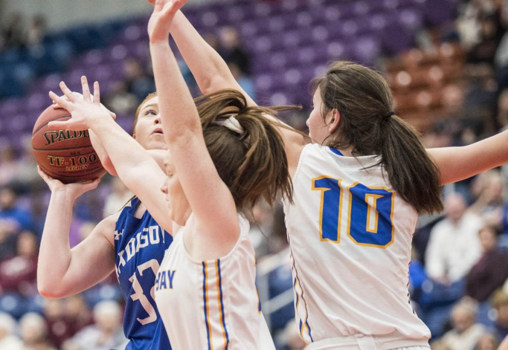 Madison's Lauren Hay, left, takes a shot as she is defended by Boothbay's Glory Blethen (10) and Josey Smith, center, in the Class C South semifinals Thursday at the Augusta Civic Center.