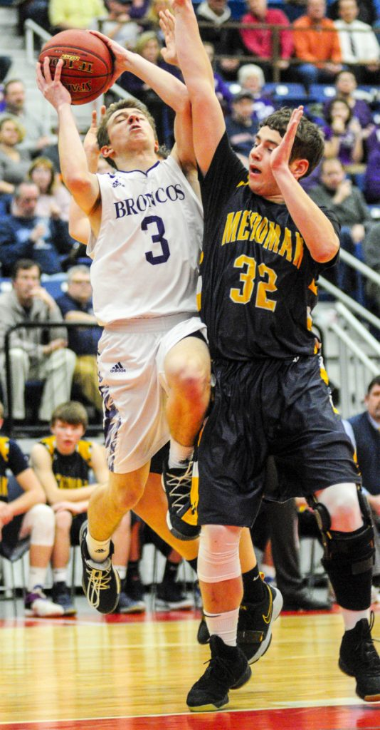 Hampden Academy's Kory Winch, left, shoots over Medomak's Nathan Emerson during the Class A North championship game Friday night at the Augusta Civic Center.