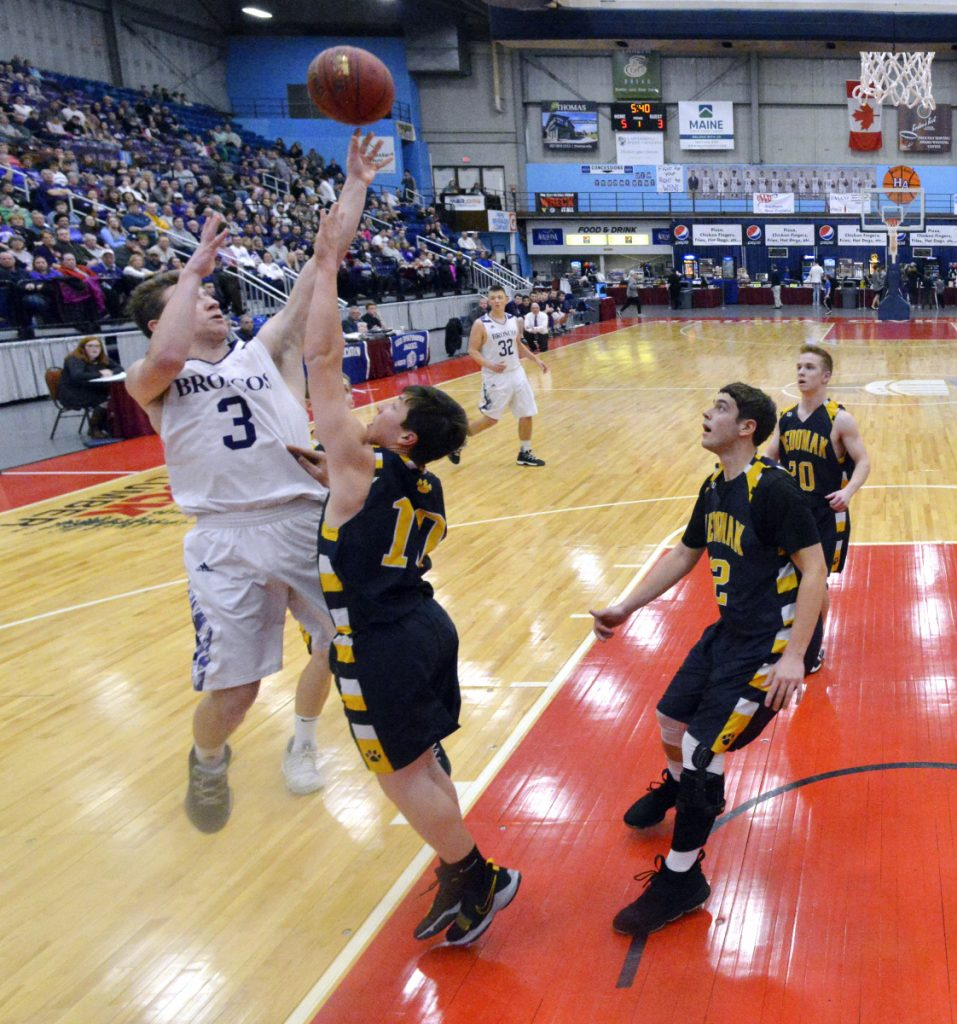 Hampden's Kory Winch, left, shoots over Medomak's Ryan Creamer during the Class A North championship game Friday night at the Augusta Civic Center.