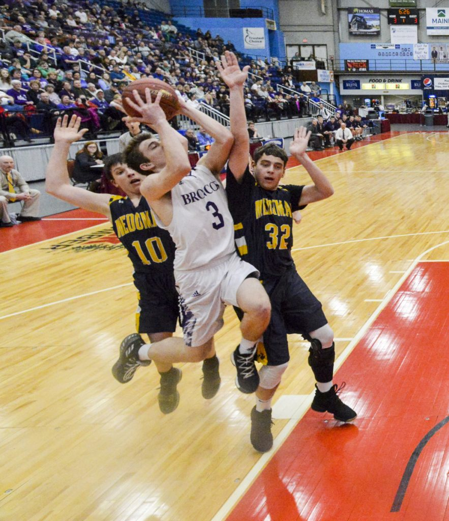 Medomak Valley's Jordan Powell, left, and Nathan Emerson, right, defend Hampden's Kory Winch during the Class A North championship game Friday night at the Augusta Civic Center.
