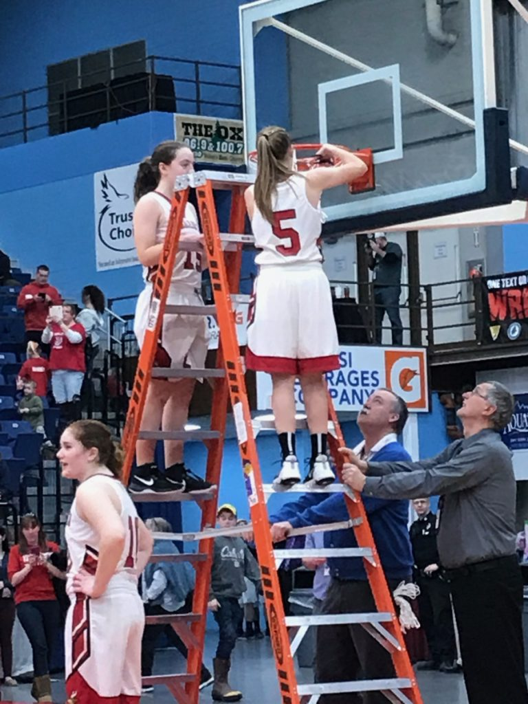Vinalhaven captain Paige Dennison cuts down one of the nets at the Augusta Civic Center after the Vikings upended Rangeley 59-49 in the Class D South title game Saturday.