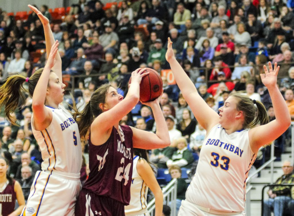 Monmouth's Kaeti Butterfield, center, tries to shoot between Boothbay defenders Page Brown, left, and Emma Brewer during the Class C South title game Saturday at the Augusta Civic Center.