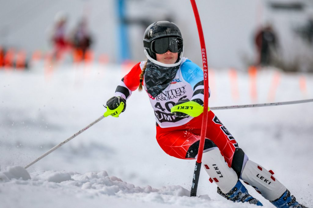 Edward Little's Jordan Cummings cross blocks a gate during her second run in the slalom event at the class A alpine championships at Black Mountain of Maine in Rumford. Cummings finished 14th helping her team come away with a second place finish overall.