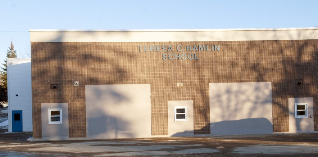 School officials have postponed a vote on closing the Teresa C. Hamlin School in Randolph.