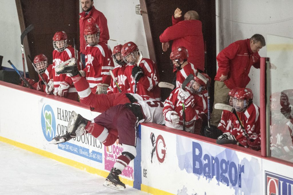 Bangor's Ethan Scripture (5) checks Cony High School's Cole Lockhart into the Cony bench during the second period Tuesday at Sawyer Arena in Bangor.