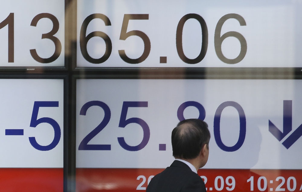 A man looks at numbers showing the downturn Friday on an electronic stock board at a securities firm in Tokyo.