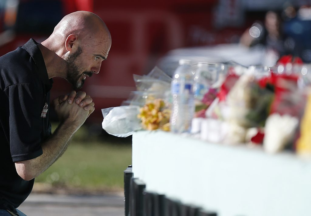 Kevin Siegelbaum, a special education teacher at Marjory Stoneman Douglas High School, leans in to pray Thursday, Feb. 15, 2018, in Parkland, Fla., during a community vigil at Pine Trails Park for the victims of the shooting at Marjory Stoneman Douglas High School. Nikolas Cruz, a former student, was charged with 17 counts of premeditated murder on Thursday.