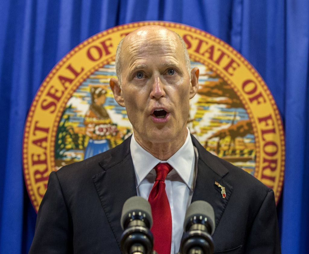 Florida Governor Rick Scott lays out his school safety proposal during a press conference at the Florida Capitol in Tallahassee, Fla., Friday, Feb 23, 2018. Scott proposed banning the sale of firearms to anyone younger than 21 as part of a plan to prevent gun violence.