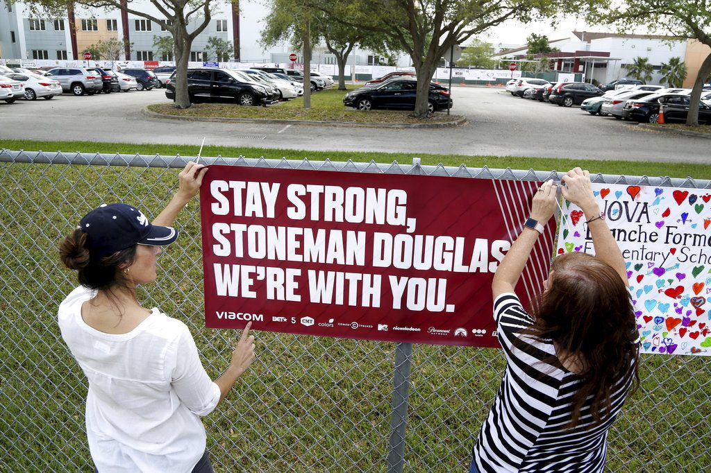 Volunteers hang banners at Marjory Stoneman High School in Parkland, Fla., to welcome back students who will be returning to school Wednesday two weeks after the mass shooting that killed 17 students and staff.