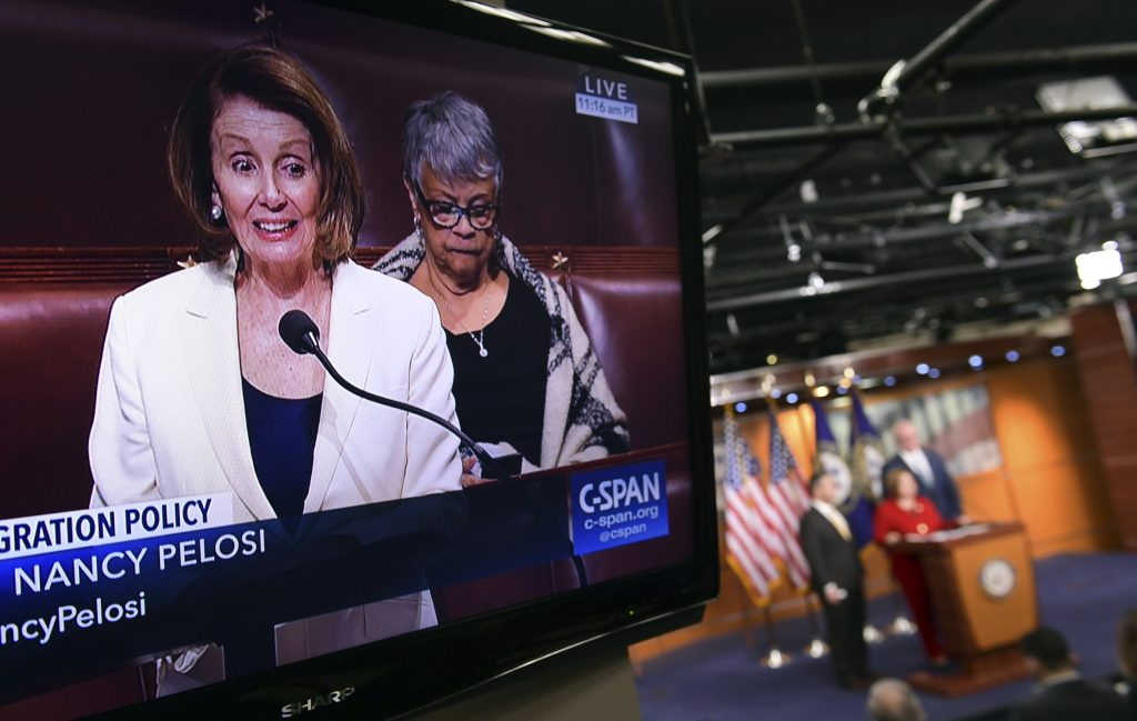 House Minority Leader Nancy Pelosi of Calif., is shown on television as she speaks from the House floor on Capitol Hill in Washington, Wednesday, Feb. 7, 2018, as a news conference that she was supposed to attend goes on in the background.
