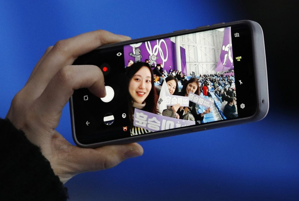 A spectator takes a selfie when waiting for the mass start speedskating races at the Gangneung Oval at the 2018 Winter Olympics in Gangneung, South Korea, Saturday, Feb. 24, 2018. (AP Photo/Vadim Ghirda)