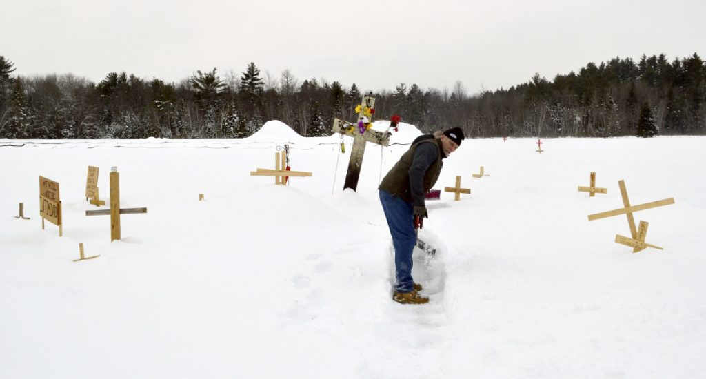 Fred Butman clears a path in the snow at the memorial he and his family built in Canaan, N.H., for his stepson Jesse James Champney, who was shot dead by police.