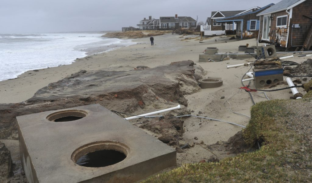Peter Cook walks the beach to check out the scene at the end of Whitecap Lane in Sandwich, Massachusetts, which was hard hit again by the overnight high tide, on Saturday.