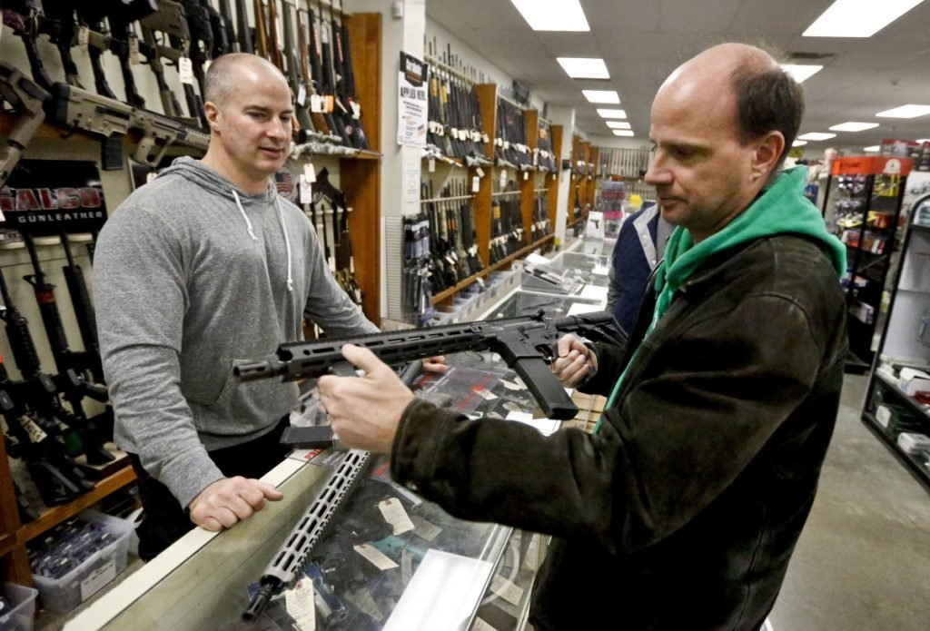 Wes Morosky, left, owner of Duke's Sport Shop in New Castle, Pa., helps Ron Detka as he shops for a rifle Friday. Morosky said business has gone up recently, but that's thanks to the annual infusion of tax refund checks.