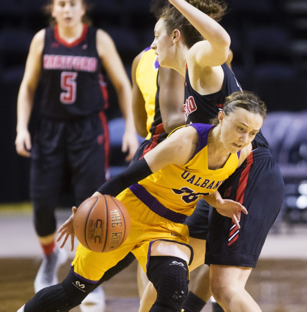 Albany guard Mackenzie Trpcic tries to drive past Hartford's Darby Lee during their America East semifinal Sunday at Cross Insurance Arena. Hartford upset the six-time defending champions, 58-56.