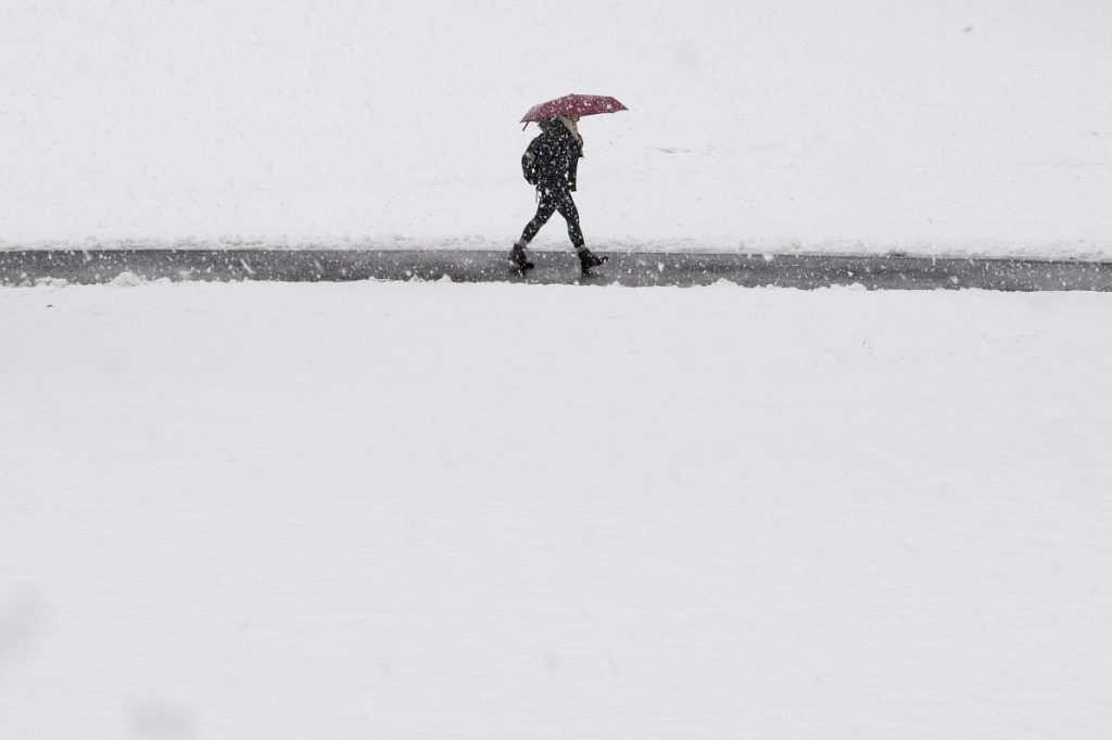 A woman shields herself from the snow with an umbrella as she walks through campus grounds at Swarthmore College in Swarthmore, Pa., on Wednesday.