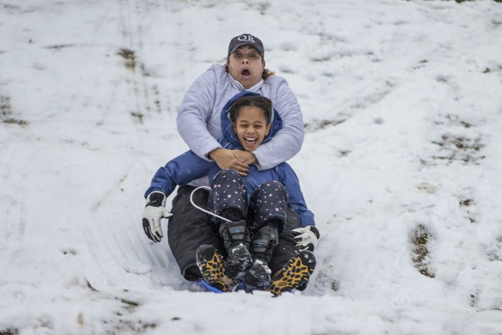 Bridget Mitchell, back, sleds down the Water Tower hill in Chestnut Hill with her daughter, Olivia Mitchell, 9, in Philadelphia on Wednesday.
