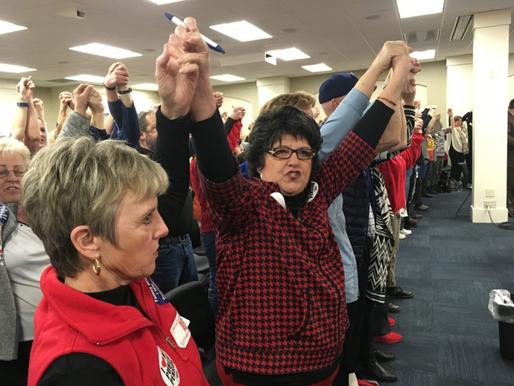 "Retired teacher Meg Judd raises her arms and chants ""Find funding first!"" during a legislative committee hearing in Frankfort, Ky.,  on Wednesday. Lawmakers voted to advance a bill that would reduce annual cost-of-living benefits for retired teachers to 1 percent from 1.5 percent."
