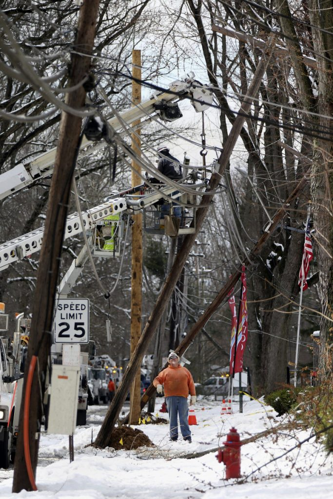 Crews work to replace utility poles in Fairless Hills, Pa., on Thursday.