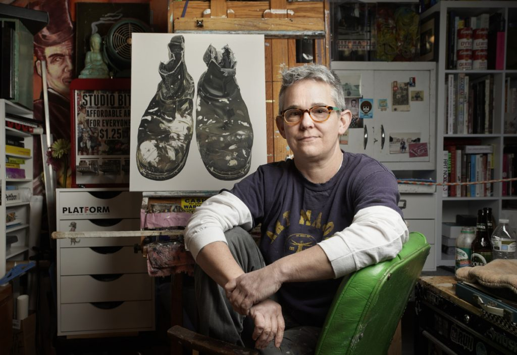 Artist Kelly Jo Shows in her Kennebunk studio. The Center for Maine Contemporary Art is exhibiting her collection of paintings of people's shoes, which she approaches as a portrait process. Behind her is a work in progress of the shoes of local artist Gil Corral.