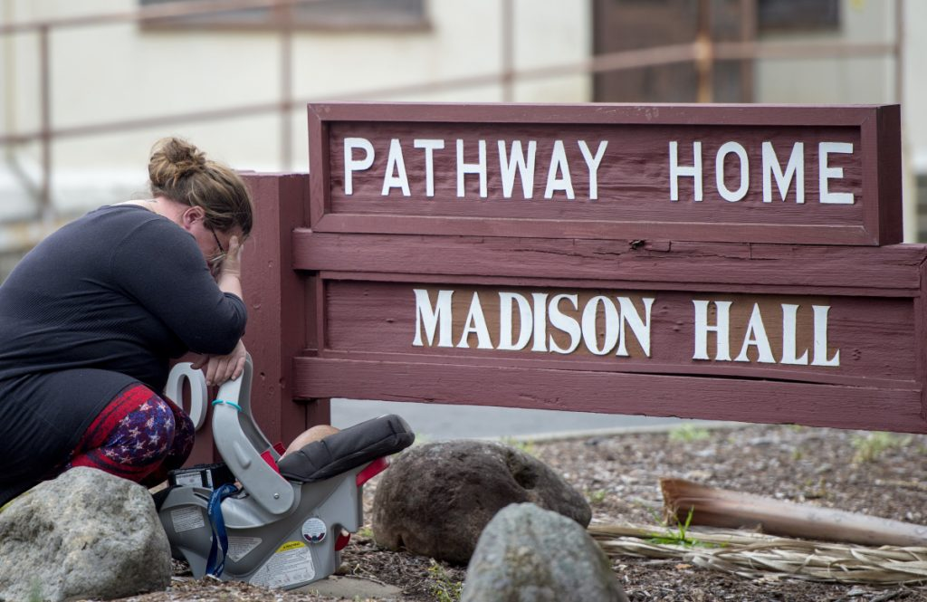 A woman who declined to give her name cries after placing flowers at a sign at the Veterans Home of California the morning after a gunman killed three hostages and himself there, in Yountville, Calif., on Saturday.