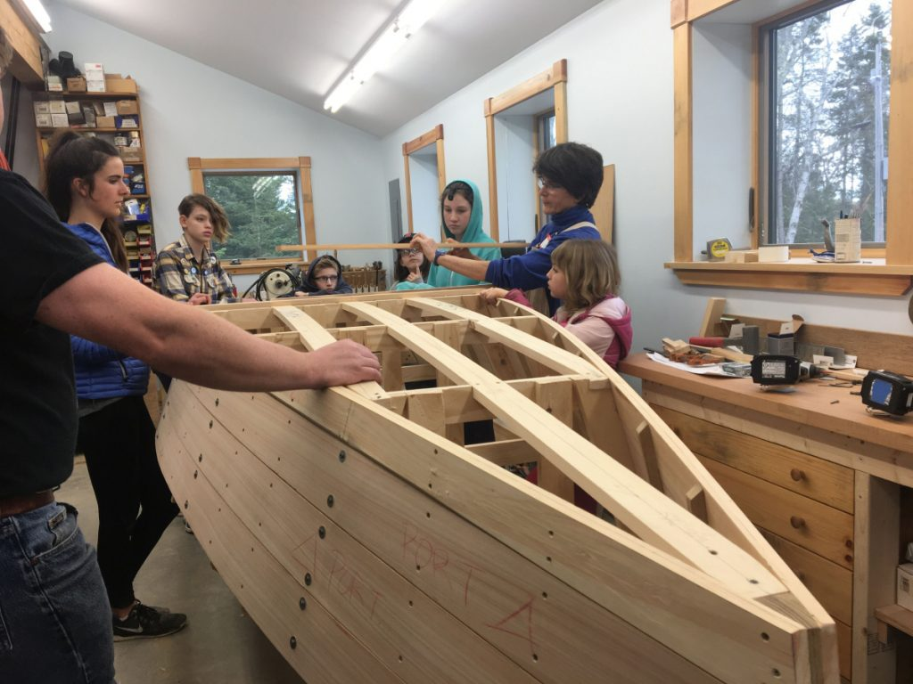 "Cundy's Harbor resident Ann Flannery works with the ""Harpswell Boat Builders,"" a free program she created for local kids ages 6 and older. When the rowboat is complete, it will be auctioned off to benefit the Holbrook Community Foundation."