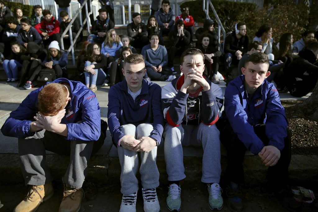 Somerville High School students sit on the sidewalk during a student walkout at the school in Somerville, Mass., on Feb. 28. A nationwide large-scale, coordinated demonstration is planned for this Wednesday.