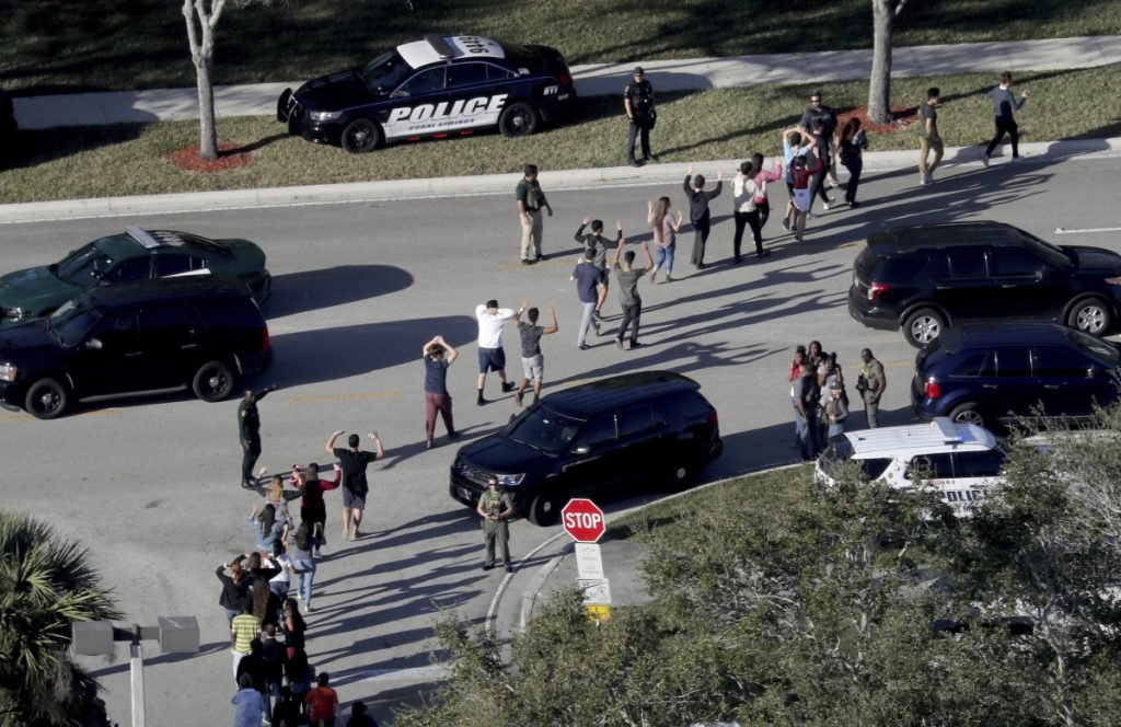 Students hold their hands in the air as they are evacuated by police from Marjory Stoneman Douglas High School in Parkland, Fla., after a shooter opened fire on the campus. Prosecutors announced they will seek the death penalty in the case.
