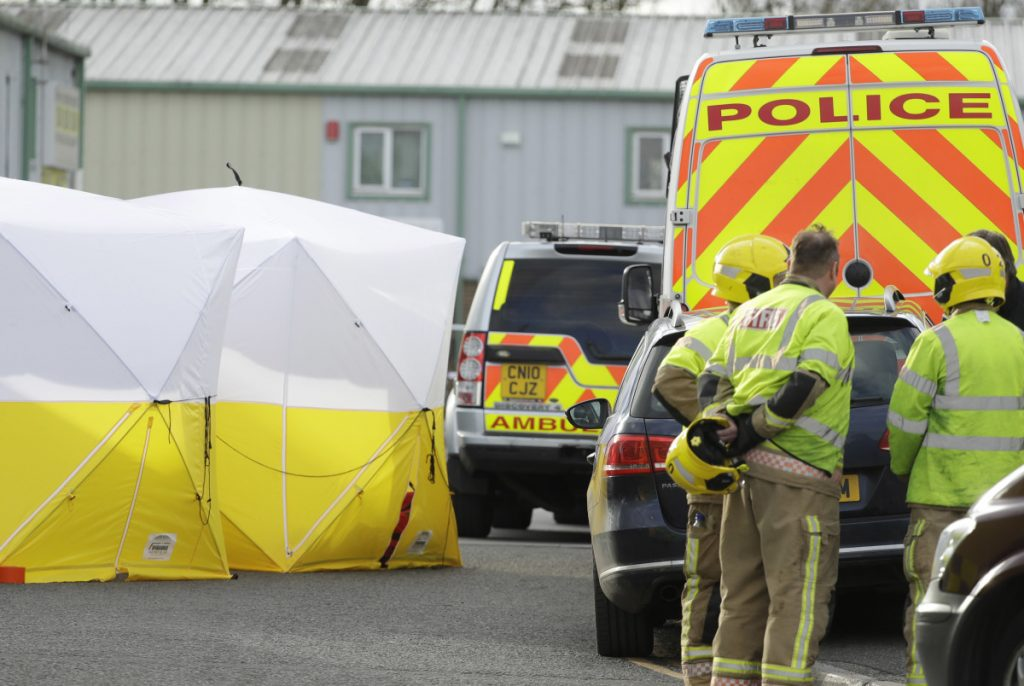 Officials at a vehicle recovery business in Salisbury, England, Tuesday, look for clues in the poisoning of a former spy and his daughter. The father and daughter are in critical condition.