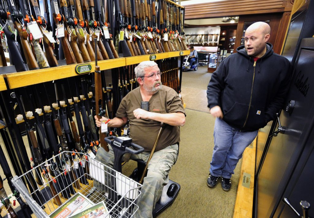 Two men converse near a gun display at the Cabela's store in Dundee, Mich. For many large outdoor stores, hunters account for a big part of their annual bottom line.