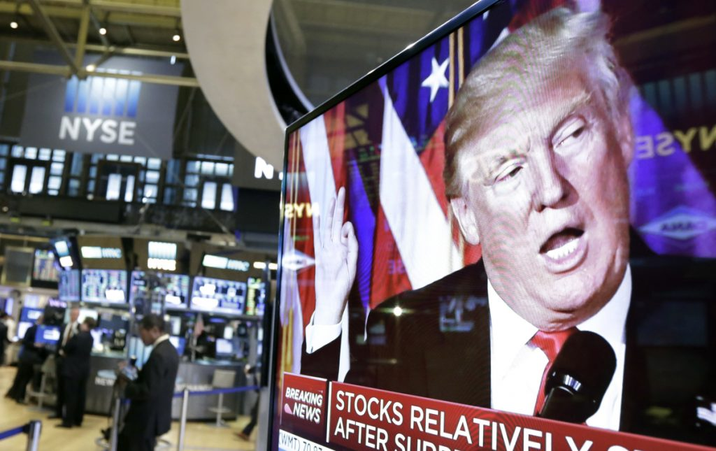 An image of President-elect Donald Trump appears on a TV screen near the floor of the New York Stock Exchange in November 2016. The stock markets have become sensitive to his decisions affecting global trade.