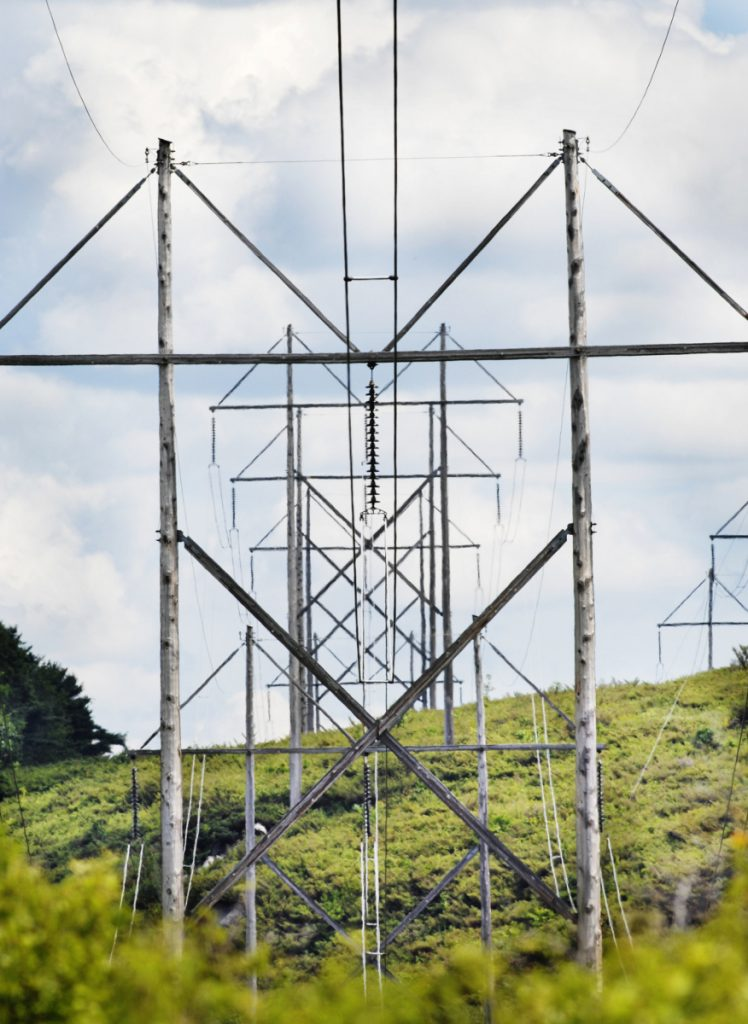 Central Maine Power's bid to build a 145-mile transmission line from the Canadian border that would supply renewable energy to Massachusetts received a major boost when the New Hampshire site panel ordered a delay that likely will eliminate CMP's competitor.