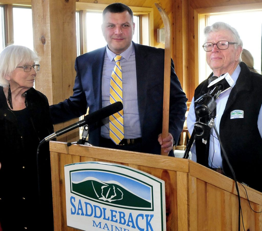 Saddleback owners Irene and Bill Berry pass the traditional wooden ski to Sebastian Monsour, center, chief executive officer of the Majella Group, during the sale announcement at the ski resort last year. The sale has yet to be completed.