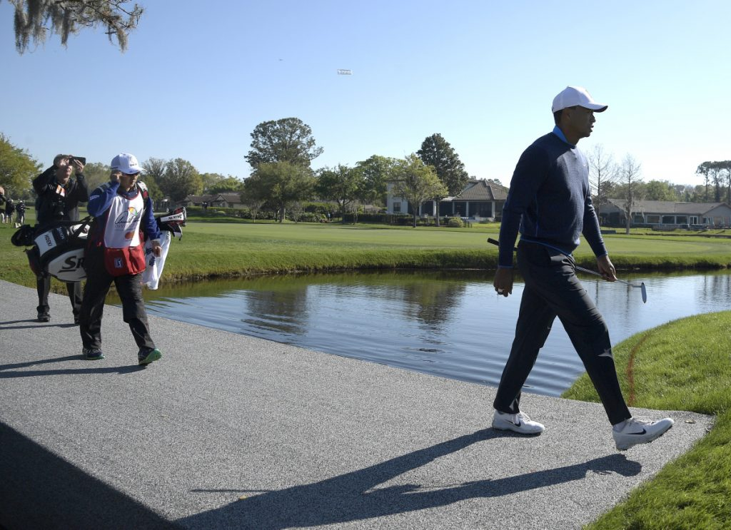 Tiger Woods crosses a bridge to the 16th green during the first round of the Arnold Palmer Invitational in Orlando, Fla. Woods keeps looking better, and shot a 68 Thursday.