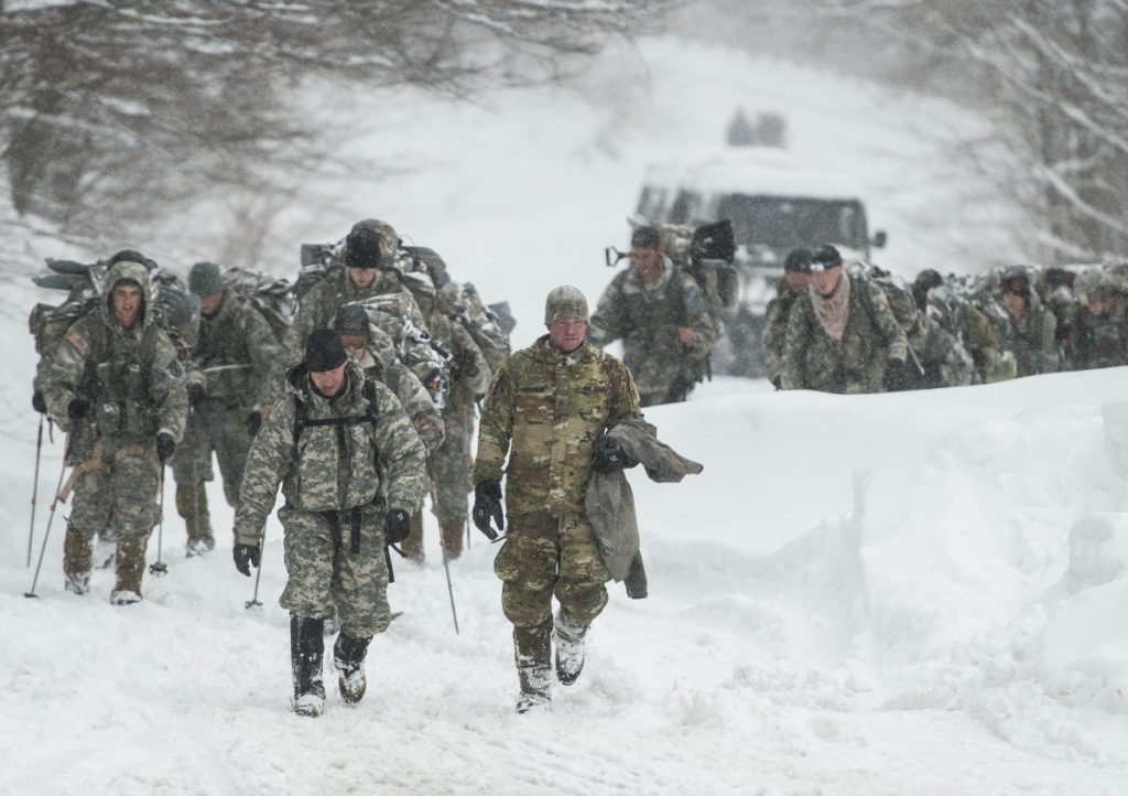 Vermont National Guard soldiers on a training exercise emerge from a closed section on Vermont 108 in Cambridge, Vermont, just below Smuggers Notch on Wednesday night after six soldiers were swept about 900 feet by an avalanche.