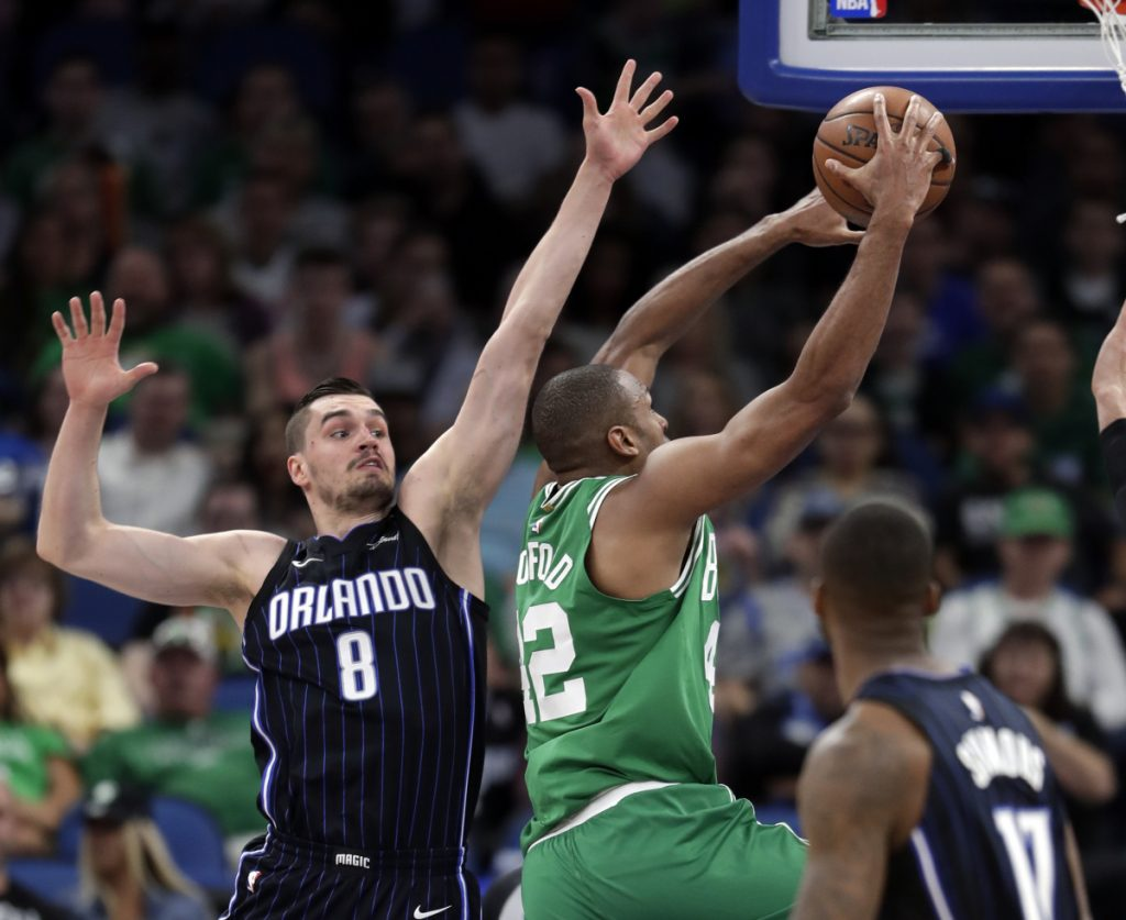 Al Horford of the Boston Celtics goes up for a shot past Mario Hezonja of the Orlando Magic during the first half of the Celtics' 92-83 victory Friday night.