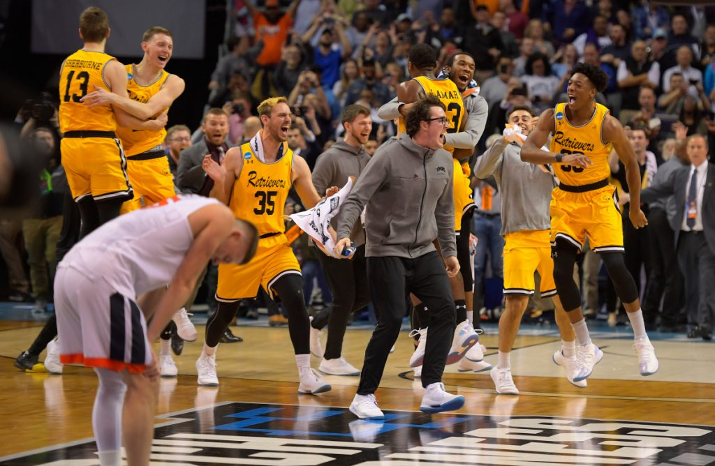 Virginia guard Kyle Guy is bent over in disappointment as UMBC players and team officials celebrate their upset of the tournament's top seed in the first round Friday night in Charlotte, North Carolina. It's the first time a No. 1 seed has been defeated by a No. 16 seed in men's tournament history.