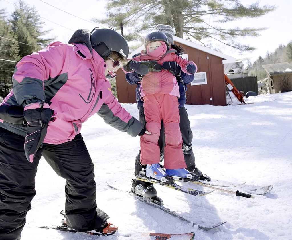 Katie Creedon is helped by her mother, Jessica, left, and ski instructor Heather Stukas at Lost Valley in Auburn on Sunday. Katie has a rare genetic disorder and doctors told her parents it was unlikely she would live to be 5. She turns 6 on Wednesday.