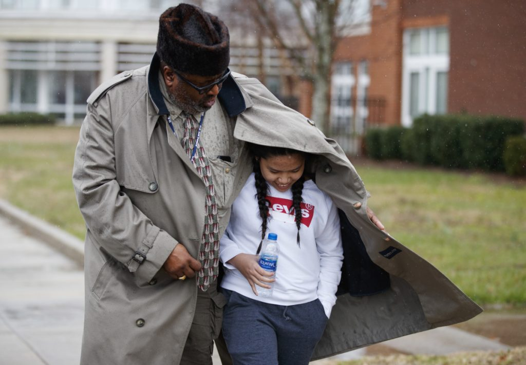 A father shelters his daughter, a student from Great Mills High School, from the rain as he picks her up from Leonardtown High School in Leonardtown, Md., on Tuesday after Great Mills was evacuated.