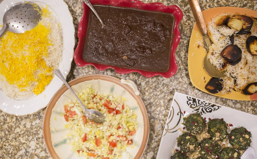 The Rohanis' meal celebrating Nowruz includes an herb-egg dish, kookoo sabzi, bottom right corner, and fesenjan, a chicken in pomegranate sauce dish, top center.