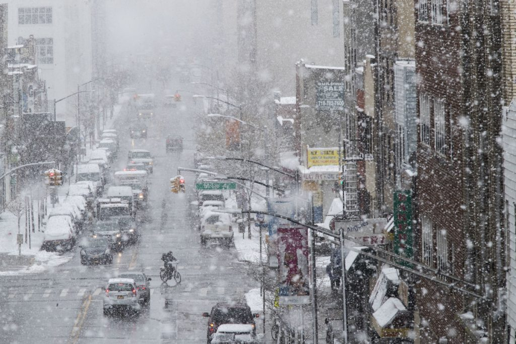Traffic makes its way along Flushing Avenue in a snow storm Wednesday in the Brooklyn borough of New York.
