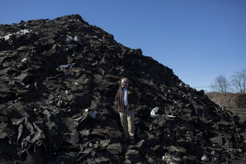 Martin Grohman, on a pile of roof shingles for recycling at the CPRC processing facility in Scarborough.