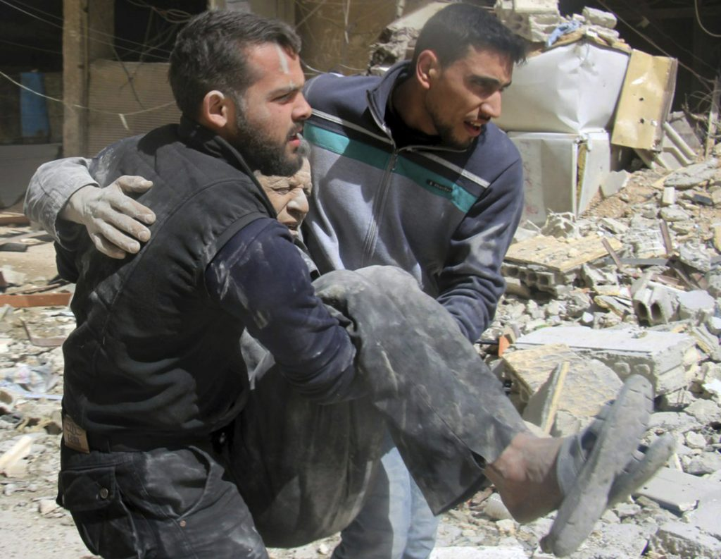 Members of the Syrian Civil Defense White Helmets carry a man who was wounded after airstrikes and shelling hit in Arbeen, in the eastern Ghouta region near Damascus, Syria.