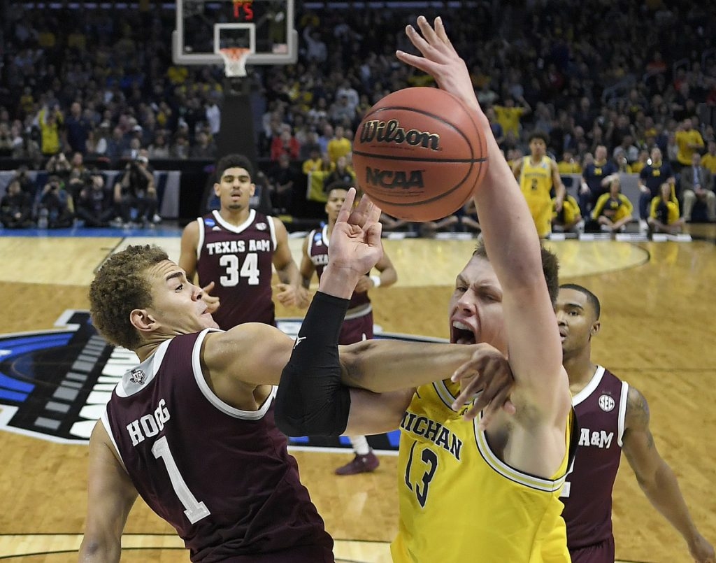 Texas A&M forward DJ Hogg, left, defends against Michigan forward Moritz Wagner in the first half of Thursday's regional semifinal in Los Angeles. The Wolvereines dominated to advance to the Elite Eight.
