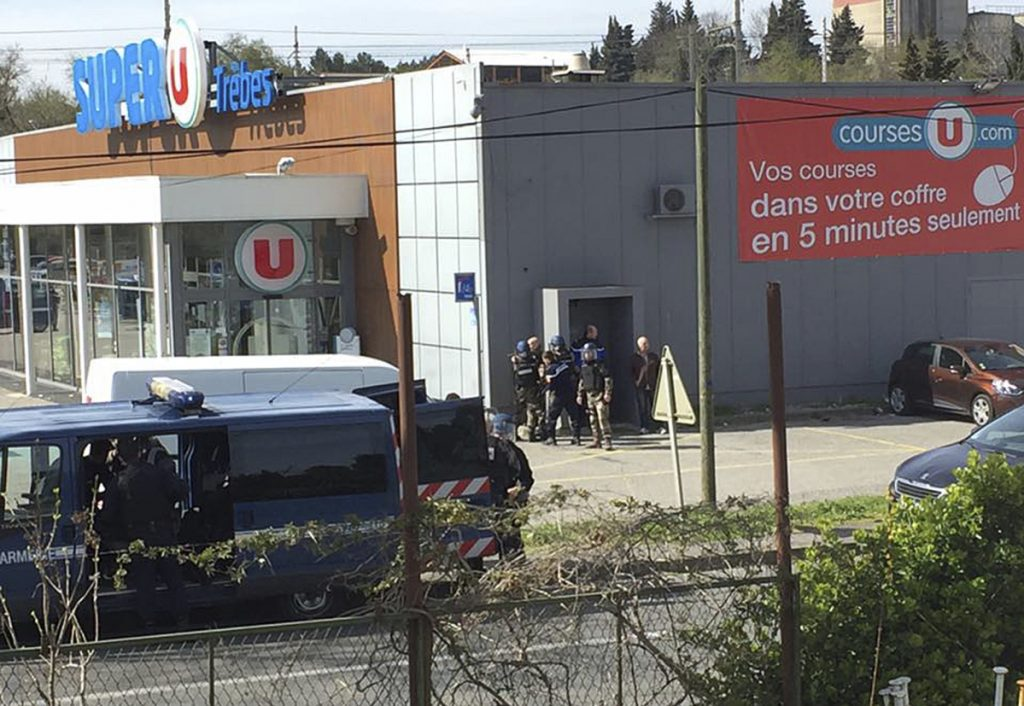Police gather outside a supermarket in Trebes, southern France, Friday March 23, 2018. An armed man took hostages in a supermarket in southern France on Friday, killing two and injuring about a dozen others, police said. He had earlier opened fire on officers nearby.(Newsflare/Tarbouriech Roseline via AP)