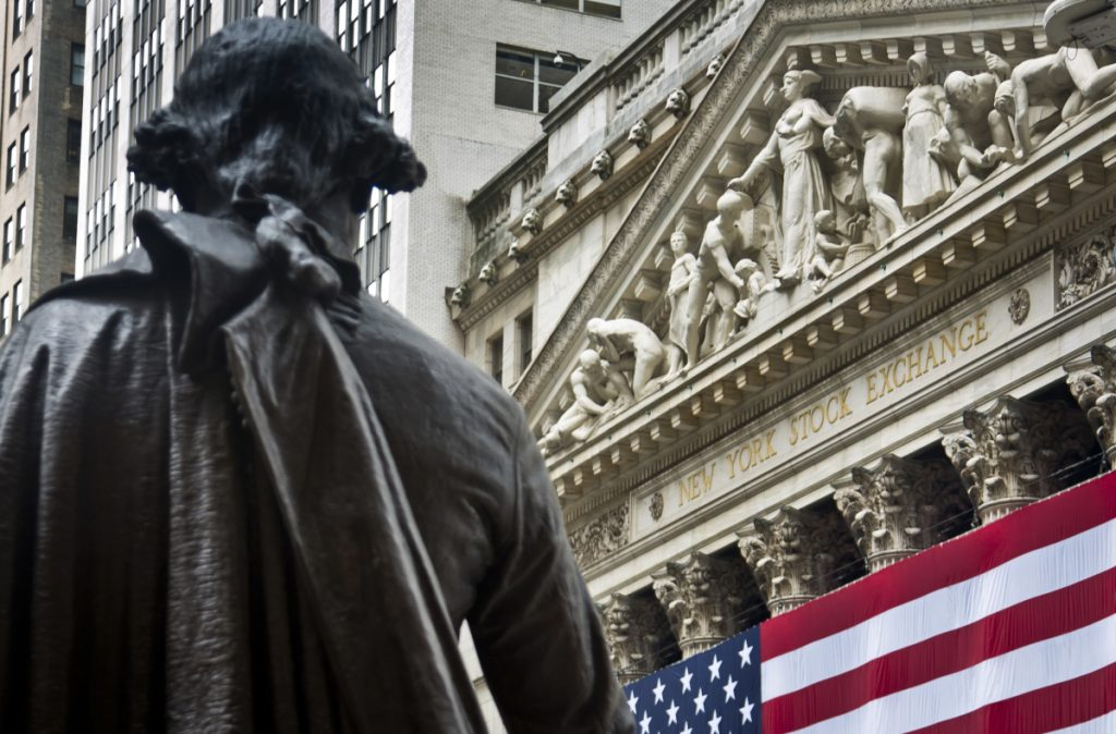 Federal Hall's George Washington statue stands near the flag-covered pillars of the New York Stock Exchange.
