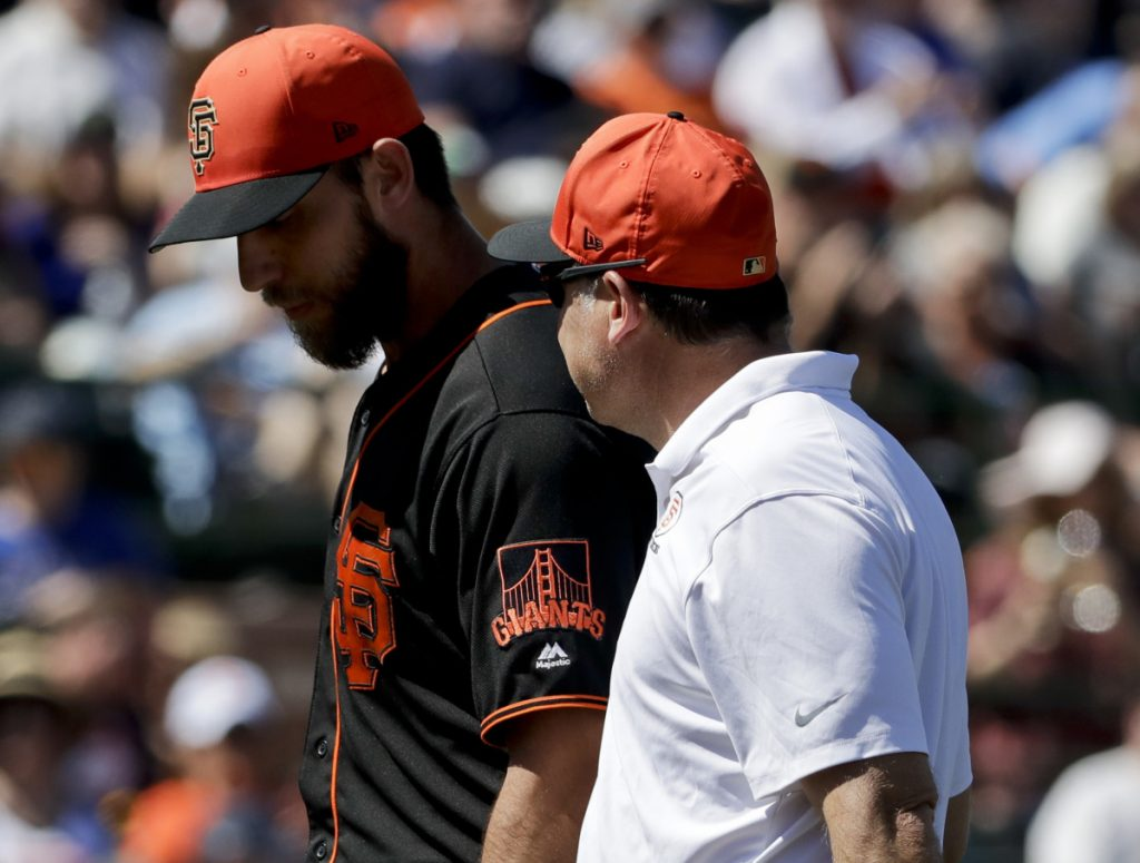 Pitcher Madison Bumgarner of the San Francisco Giants walks off the field with a trainer Friday after a line drive broke a bone in his pitching hand during a spring-training game